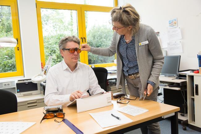 Frau berät einen Mann es werden unterschiedliche Brillengläser getestet
